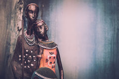 African statue of a girl with the young men from ethnic blue with ocher background behind Royalty Free Stock Image