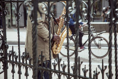 African street musician playing jazz on saxophone throw lattice with bicycle silhouette, city life in Amsterdam Royalty Free Stock Image