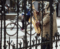 African street musician playing jazz on saxophone throw lattice Stock Images