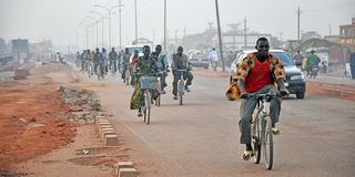 African street. The photo shows people returning home from work on a peripheral road of Ouagadougou, capital of Burkina Faso Stock Photos