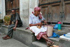 African street traders sit at the of closed Trade Rows. Royalty Free Stock Image