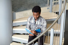 African student boy or man reading book on stairs Stock Image