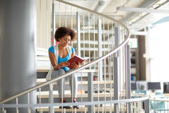 African student girl reading book at library. Education, high school, university, learning and people concept - smiling african american student girl reading Royalty Free Stock Image