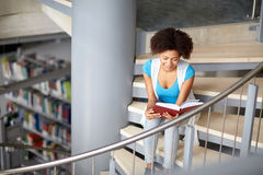 African student girl reading book at library. Education, high school, university, learning and people concept - smiling african american student girl reading Stock Photo