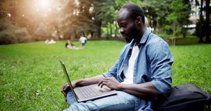 African student with laptop on lawn sunset stock video footage