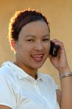 African student with phone. A beautiful colored multiracial African teenager girl head portrait with an excited expression in the pretty face saying HELLO and Royalty Free Stock Images