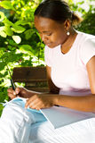 African student studying. Happy african american college student studying outdoors Royalty Free Stock Images