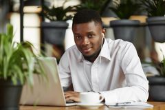 African student typing at laptop working in restaurant. Stock Image