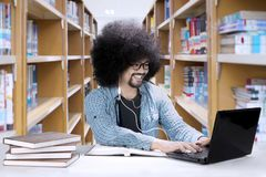 African student using earphones in the library. African male student using earphones while learning with laptop and books in the library Stock Photography