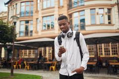 African man walking and looking at electronic map in smart phone. African student walking at street holding one hand in pocket and in other smart phone, writing royalty free stock images