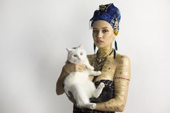African style girl with a cat on your hands. Duvet in African-style clothes, blue headscarf. In the ears are big earrings. Holds a white cat stock photography