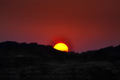 African Sun Set. A large orange African sun setting behing a hill in the south african desert Stock Photography