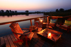 African Sundowner. Enjoy a refreshing sundowner in cozy ambiance at the bank of smooth Kwando River in the Caprivi Strip, Namibia Royalty Free Stock Image