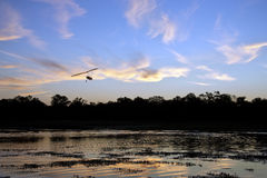 African Sunset - Okavango Delta - Botswana. A microlight aircraft flying over a channel in the Okavango Delta in Botswana at sunset Stock Photography