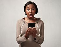 African surprised woman with smartphone Royalty Free Stock Photo