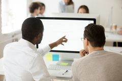 African team leader explaining colleague corporate application u. Rear view of african team leader explaining caucasian colleague corporate software usage, black stock photos
