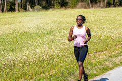 African teen girl jogging next to flower field. Royalty Free Stock Image