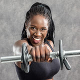 African teen girl shouting with dumbbell. stock photos