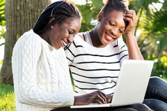 African teen girls having fun on laptop in park. Close up outdoor portrait of two afro american teen girls socializing on laptop in park Royalty Free Stock Images