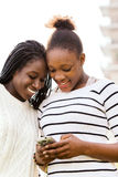 African teen girls texting on smart phone.