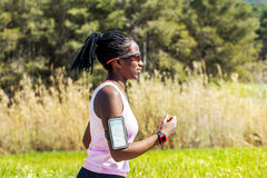 African teen running with fitness activity tracker. Action shot of young african woman jogging with smart watch and smart phone. Attractive teen tracking Royalty Free Stock Images