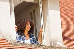 African teenage girl in country house attic window. Portrait of beautiful African teenage girl in country house attic window royalty free stock photos
