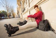 Teenage girl in rollerblades sitting at sidewalk Royalty Free Stock Photography