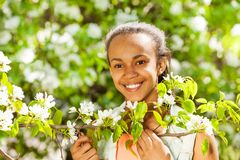 African teenager girl holds white pear flowers Royalty Free Stock Images