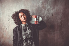 African teenager girl with skateboard in front of a concrete wall Stock Photography