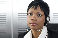 African Telesales. Closeup of young attractive african call center agent talking on the headset in a modern office setting Stock Images