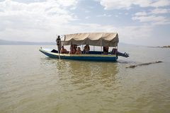 African tourism. On the Lake Chamo at the Nechisar National Park, Ethiopia. The crocodile (Crocodilus niloticus) is swimming around the tourists boat Royalty Free Stock Photography