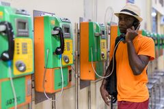African tourist man talking on payphone and thinking. Young black African tourist man talking on payphone while thinking inside the railway station in Bangkok royalty free stock photography