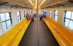 African Train. A perspective shot of the inside of railroad caboose with people in long yellow seats which runs all the way down the coast of Cape Town, South royalty free stock photography