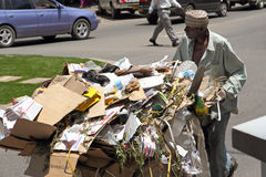 African Trash Man. A African man in Mwanza, Tanzania pushing a cart full of cardboard boxes and trash royalty free stock image