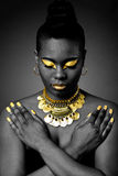 African tribal in gold. Beautiful African tribal fashion with gold eyeshadow and necklace on dark with arms crossed and looking down Stock Photo