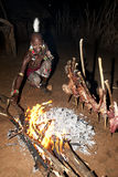 African tribal man of the Hamer ethnic roast Goat. African tribal man of the Hamer ethnic group with traditional clothes and ornaments Royalty Free Stock Images