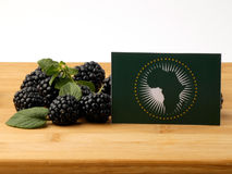 African Union flag on a wooden panel with blackberries isolated Royalty Free Stock Photos