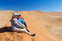African vacation holiday, tourists sitting on dune, couple in Namib desert dunes and lanscape, travel in Namibia, Africa royalty free stock images