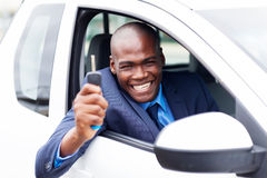 African vehicle buyer. Happy african vehicle buyer inside his new car with car key royalty free stock photography