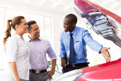 African vehicle dealer. Friendly african american vehicle dealer showing couple new car engine Stock Images