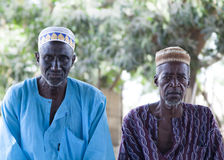 African village elders in traditional colorful clothes and muslim caps. Portrait of two african village elders in traditional clothes and muslim caps looking Royalty Free Stock Photo