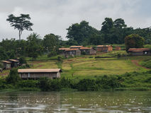 An African village is situated on the shores of the river Sangha (Republic of the Congo). A small African village is situated on the green shores of the river Stock Photos