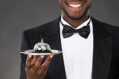 African Waiter Holding Service Bell. Portrait Of Happy African Waiter Holding Service Bell Royalty Free Stock Images