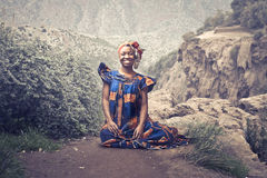 African woman. Smiling african woman in traditional dress sitting on a rock Stock Photos