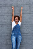 African woman with arms raised pointing up Stock Photo