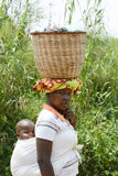African woman with basket on head and cute baby on Stock Photo