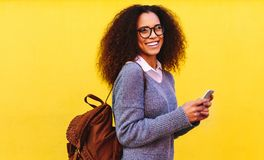 African woman with bag and phone. Portrait of african woman with curly hair wearing sweater and eyeglasses standing against yellow background with a bag and royalty free stock photography