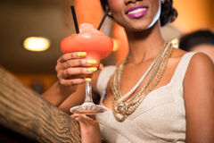 African Woman in bar drinking cocktail. African Woman with golden necklaces in a bar drinking frozen daiquiri Royalty Free Stock Photography