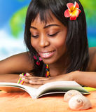 African woman on the beach. Photo of beautiful african woman read book on the beach, pretty black female enjoying summer vacation, cute young lady with red Stock Images