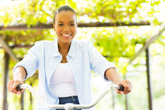 African woman bike. Pretty african woman riding a bike outdoors Royalty Free Stock Photography